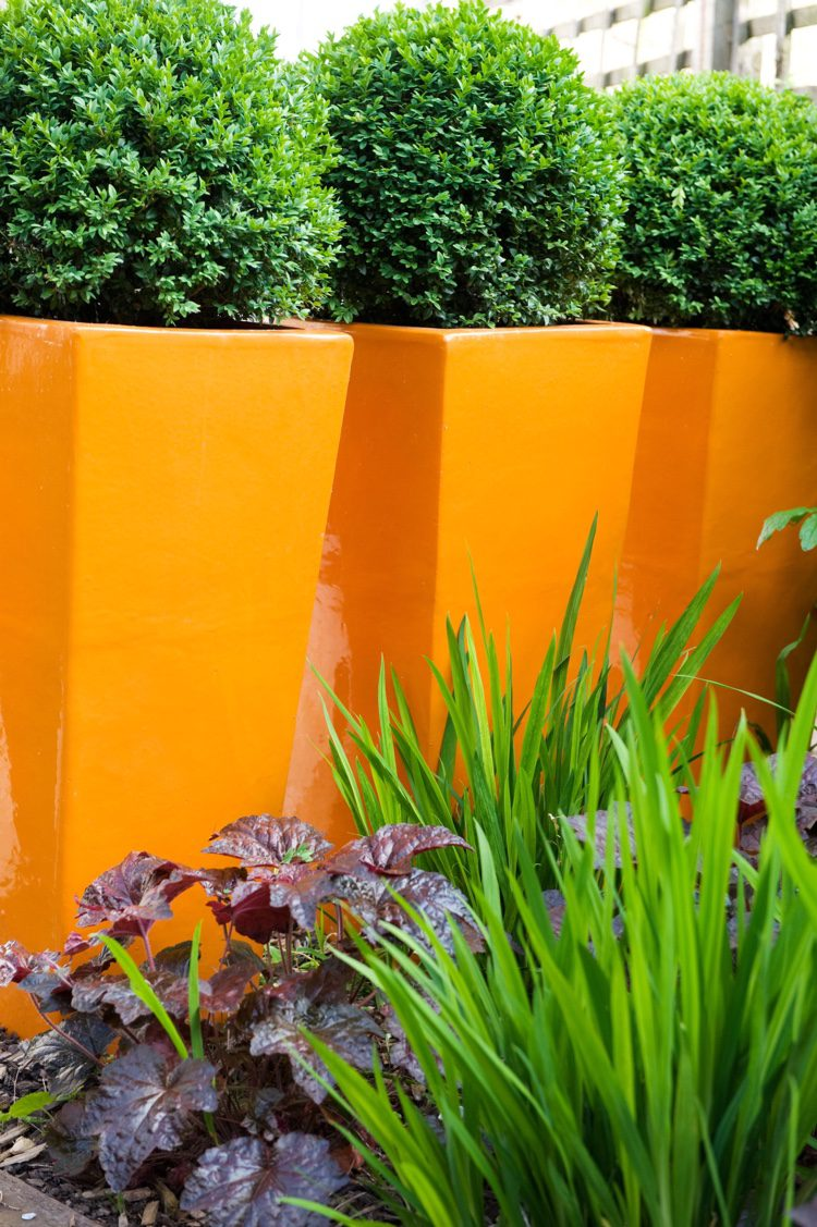 Position brightly coloured fibre glass planters in threes for great colour blocking
